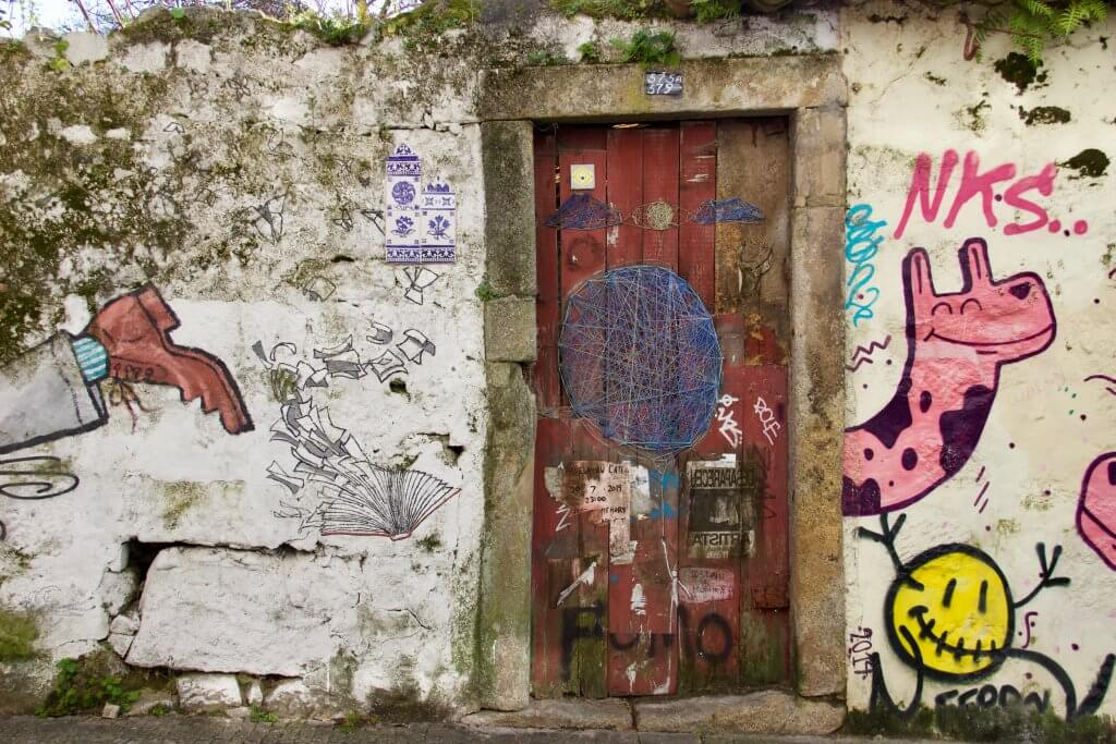 An old door surrounded by funky street art and azulejos tiles in Porto, Portugal. ©KettiWilhelm2020