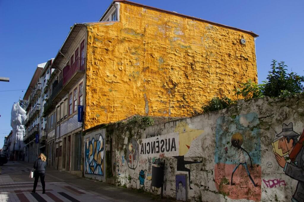 Street art, graffiti and a woman walking by a bright yellow building in Porto. ©KettiWilhelm2020